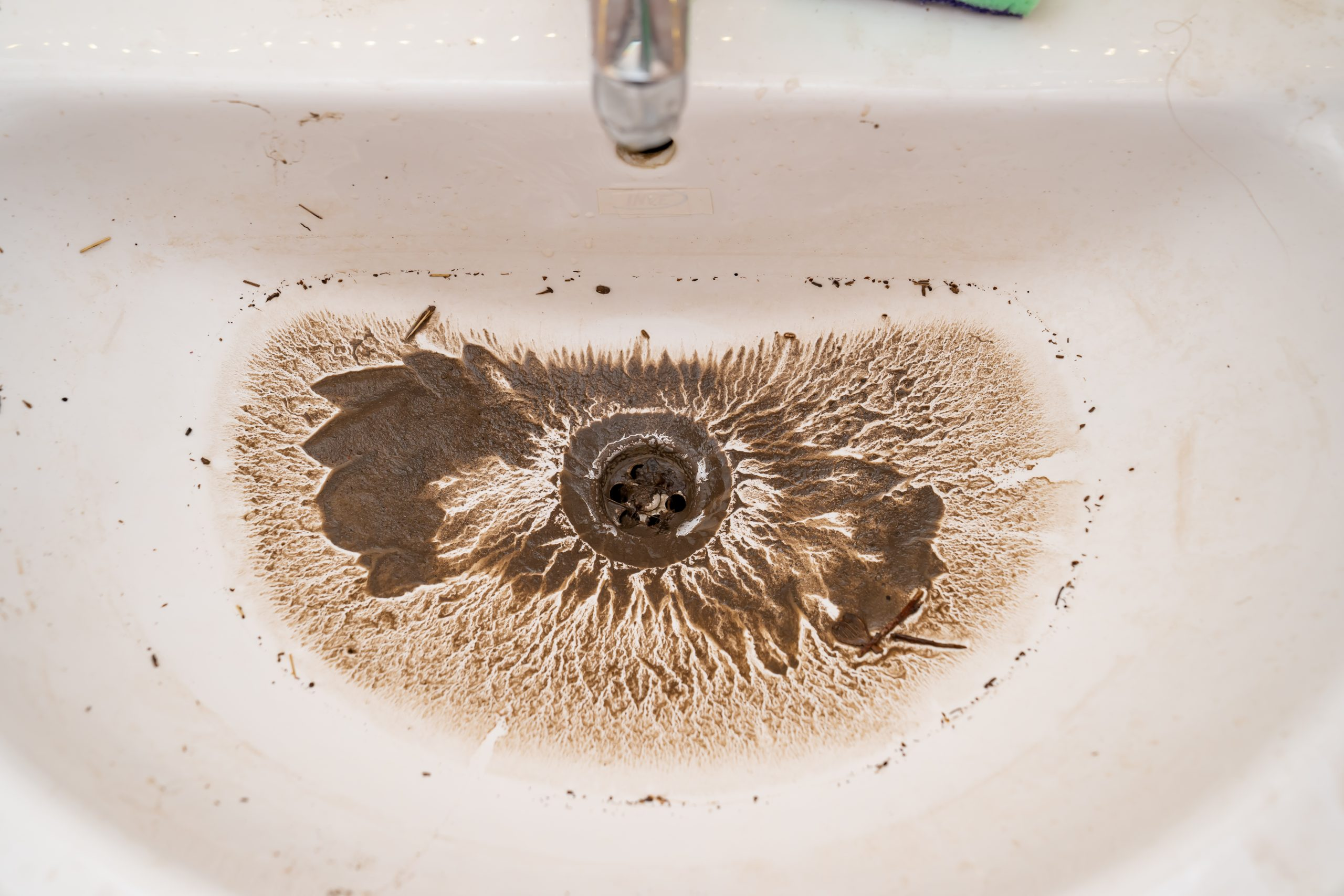 water drains into the dirty sink drain after the blockage is removed